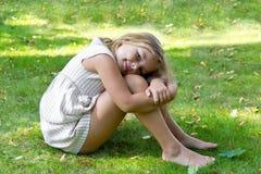 Fille mignonne s'asseyant sur l'herbe verte Images libres de droits