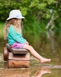 Fille mignonne s'asseyant sur la banque photo libre de droits