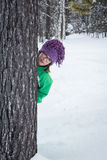 Fille mignonne se cachant derrière un arbre dans la forêt neigeuse Photographie stock