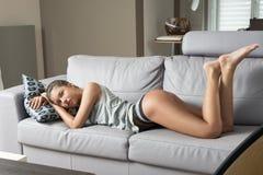 Fille mignonne se trouvant sur le divan Image libre de droits