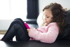 Fille mignonne se trouvant sur le sofa avec la tablette images stock