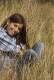 Fille mignonne souriant dans l'herbe grande Photos stock