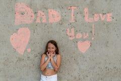 Fille mignonne souriant sur le fond du mur avec le papa de mots je t'aime Concept de f?te des p?res heureuse images libres de droits