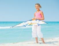 Fille mignonne sur la plage jouant avec un cerf-volant coloré Image libre de droits