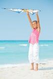 Fille mignonne sur la plage jouant avec un cerf-volant coloré Images libres de droits