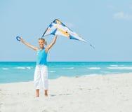 Fille mignonne sur la plage jouant avec un cerf-volant coloré Photos libres de droits