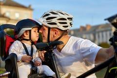 Fille mignonne sur le siège de vélo faisant un cycle avec le père dans la ville Photographie stock libre de droits