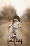 Fille mignonne sur le tricycle tout au sujet des accessoires Image stock