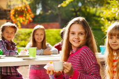Fille mignonne tenant le petit gâteau et la tasse avec ses amis Images stock
