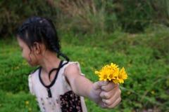 Fille mignonne thaïlandaise avec les fleurs jaunes photographie stock libre de droits