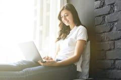 Fille millénaire heureuse avec l'ordinateur portable sur le rebord de fenêtre Portrait de jeune femme avec l'espace de diastema e Photographie stock libre de droits