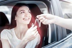 Fille millénaire rayonnante recevant des clés de voiture de l'homme image stock