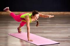 Fille mince d'athlète de jeune femme de forme physique faisant l'exercice avec des jambes sur le tapis rose de yoga Photos stock