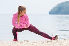 Fille mince dans des vêtements sportifs s'exerçant sur la plage en mer, concept actif sain de mode de vie Image stock
