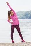Fille mince dans des vêtements sportifs s'exerçant sur la plage en mer, mode de vie actif sain Photo libre de droits