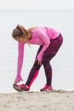 Fille mince dans des vêtements sportifs s'exerçant sur la plage en mer, mode de vie actif sain Photographie stock