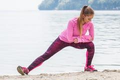 Fille mince dans des vêtements sportifs s'exerçant sur la plage en mer, mode de vie actif sain Images libres de droits