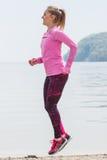 Fille mince dans des vêtements sportifs s'exerçant sur la plage en mer, mode de vie actif sain Image stock