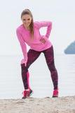 Fille mince dans des vêtements sportifs s'exerçant sur la plage en mer, mode de vie actif sain Photo stock