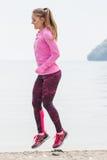 Fille mince dans des vêtements sportifs s'exerçant sur la plage en mer, mode de vie actif sain Image libre de droits