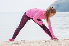 Fille mince dans des vêtements sportifs s'exerçant sur la plage en mer, mode de vie actif sain Images stock