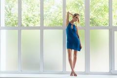 Fille mince dans la robe bleue restant sur le filon-couche de fenêtre Image stock