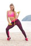Fille mince dans les vêtements de sport de centimètre s'exerçant avec des haltères sur la plage, mode de vie de sports, amincissa Photos stock