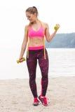Fille mince dans les vêtements de sport de centimètre s'exerçant avec des haltères sur la plage, mode de vie de sports, amincissa Photographie stock