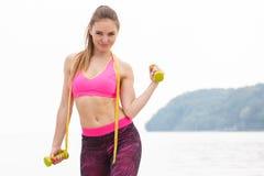Fille mince dans les vêtements de sport de centimètre s'exerçant avec des haltères sur la plage, mode de vie de sports, amincissa Images libres de droits