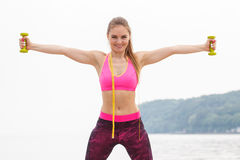 Fille mince dans les vêtements de sport de centimètre s'exerçant avec des haltères sur la plage, mode de vie de sports, amincissa Photo stock