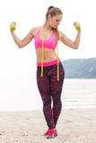 Fille mince dans les vêtements de sport s'exerçant avec les haltères sur la plage, concept de mode de vie de sports et amincissan Photographie stock libre de droits