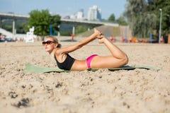 Fille mince de forme physique dans des lunettes de soleil s'étendant à la plage pendant le matin photo libre de droits