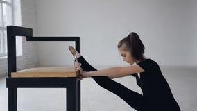 Fille mince mignonne faisant étirant des jambes se reposant dans le studio à l'intérieur Flexibilité attrayante de formation de g banque de vidéos