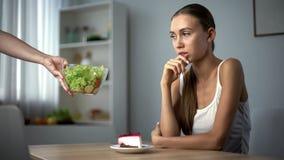 Fille mince pensant au-dessus de la décision pour manger du gâteau ou de la salade, calories contre l'alimentation saine photographie stock