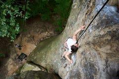 Fille mince surmontant l'itinéraire s'élevant difficile sur des roches avec la corde Extérieur extrême d'été Vue sup?rieure photos stock