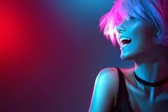 Fille modèle de beauté dans les lumières lumineuses colorées avec le maquillage à la mode Photographie stock libre de droits