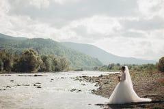 Fille, modèle, jeune mariée sur un fond de la rivière et montagnes Verticale de beauté photo libre de droits