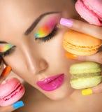 Fille modèle prenant les macarons colorés images stock