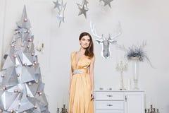 Fille modèle sexy et à la mode avec le maquillage lumineux, dans la longue robe d'or, posant près de l'arbre de Noël argenté mode images libres de droits