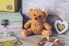 Fille molle d'ours de jouet avec un arc Jouez sur une table en bois avec une boîte et un coeur Photo stock