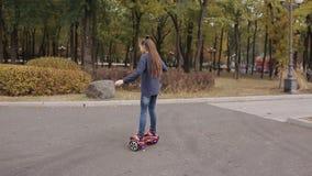 Fille montant le hyroscooter électronique portatif dehors banque de vidéos