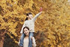 Fille montant sur le dos sur les épaules de la mère appréciant Autumn Leaves Photos stock