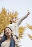 Fille montant sur le dos sur les épaules de la mère appréciant Autumn Leaves Image stock