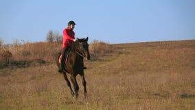 Fille montant un cheval galopant sur un pré Mouvement lent clips vidéos