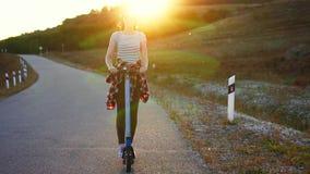 Fille montant un scooter électrique sur le coucher du soleil derrière, MOIS lent banque de vidéos