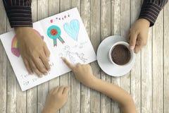 Fille montrant la peinture de main sur la carte au père Photos libres de droits