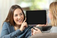 Fille montrant un écran vide de comprimé à un ami Photos libres de droits