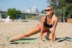 Fille musculaire de forme physique dans des lunettes de soleil s'étendant à la plage pendant le matin L'espace vide images stock