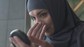 Fille musulmane saupoudrant le visage, interdiction religieuse des cosmétiques pour le plan rapproché islamique de femmes banque de vidéos