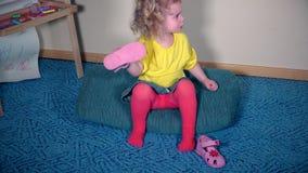 Fille nerveuse jouant avec ses chaussures La pente d'enfant a mis la sandale dessus banque de vidéos